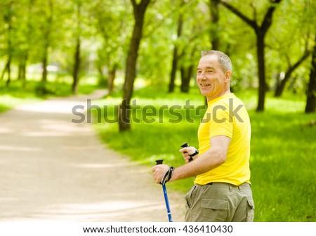 Senior man making nordic walking in the park - stock photo