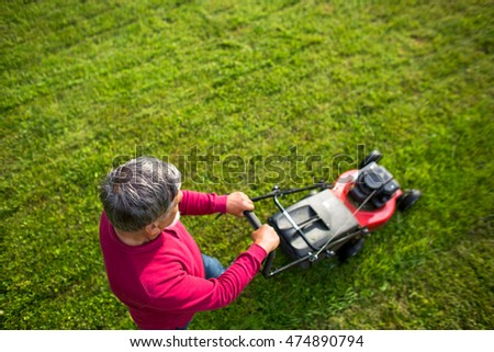 Senior man mowing his garden - shot from above - interesting angle view