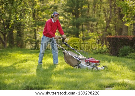Senior man mowing overgrown lawn in his yard - stock photo