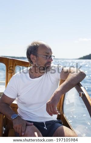 Senior man on boat, Sweden - stock photo