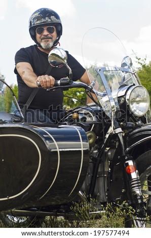 Senior man on custom sidecar motor bike smiling - stock photo