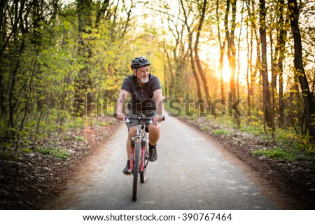 Senior man on his mountain bike outdoors (shallow DOF; color toned image) - stock photo