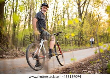 Senior man on his mountain bike outdoors (shallow DOF; color toned image) - stock photo