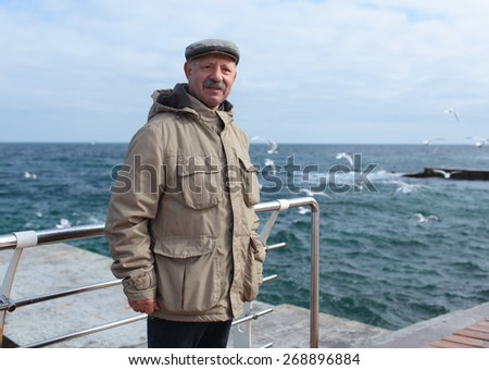 Senior man on the pier against the sea in a springtime day - stock photo