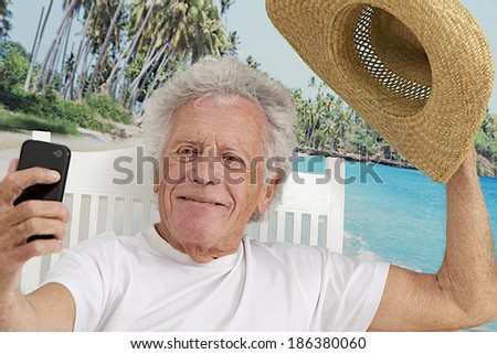 Senior man on vacation taking picture of himself on a tropical beach background with  salutation gestural to send to family - stock photo