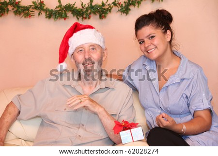 senior man or grandad with grandchild grandaughter carer on nurse in old peoples home or residential care at christmas xmas or holiday - stock photo
