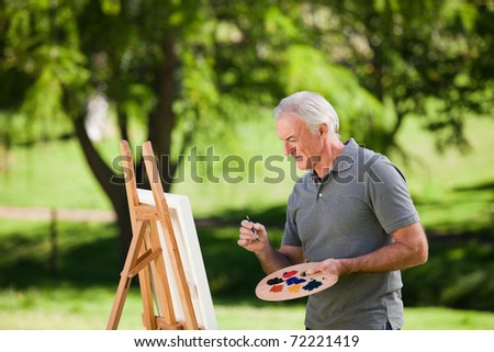 Senior man painting ouside - stock photo