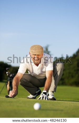 Senior man playing golf aiming for the hole, it is a wonderful clear summer late afternoon, the colors are very vivid - stock photo