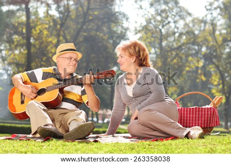 Senior man playing guitar to his wife on a picnic, seated on a blanket. The shot is in a city park during early autumn - stock photo