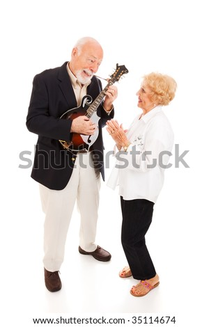 Senior man plays mandolin while his wife signs along.  Full body isolated.