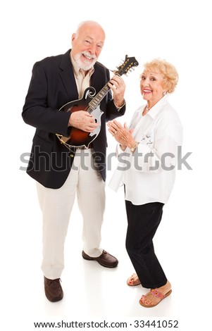 Senior man plays mandolin while his wife sings along.  Full body isolated.