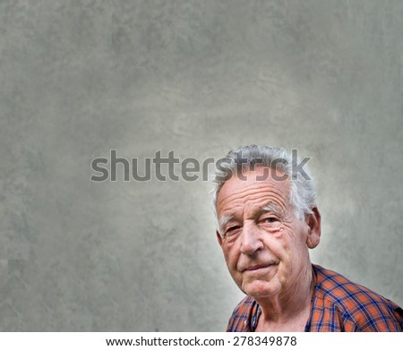Senior man portrait against grey wall as background for text - stock photo