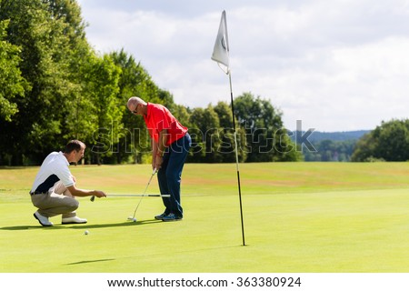 Senior man practicing golf with teacher helping - stock photo