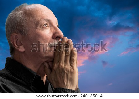 Senior man praying against blue cloudy sky - stock photo