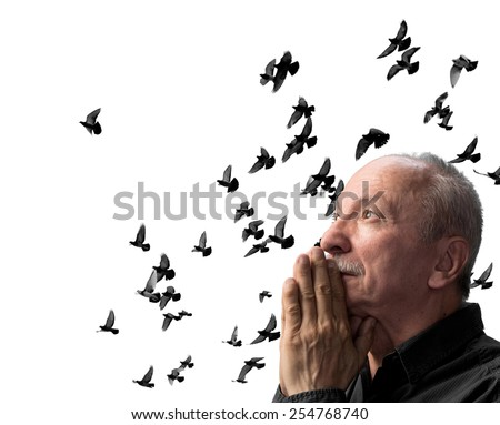 Senior man praying against the sky with flying doves - stock photo