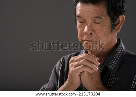 Senior man praying with his hands clasped - stock photo