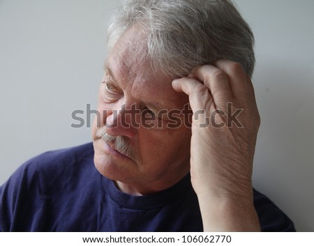 senior man preoccupied with his thoughts - stock photo