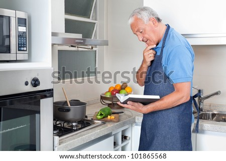 Senior man preparing food with the help of recipe book - stock photo