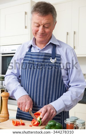 Senior Man Preparing Meal In Kitchen