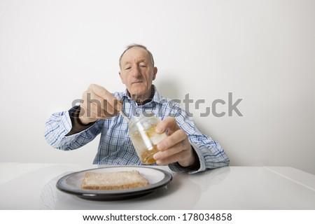 Senior man preparing slice of bread and marmalade at table - stock photo