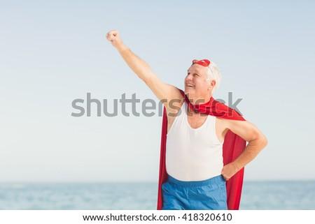 Senior man pretending to be a superhero on a sunny day - stock photo