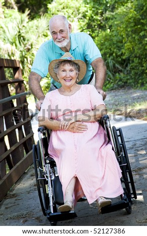 Senior man pushing his disabled wife through the park in a wheelchair.