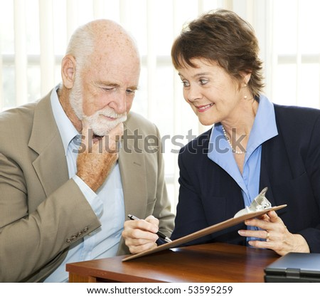 Senior man reading and thinking about a contract while eager businesswoman encourages him to sign.
