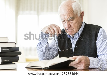 Senior man reading book relaxed at home - stock photo