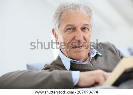 Senior man reading book relaxed in sofa - stock photo
