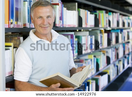 Senior man reading in a library - stock photo