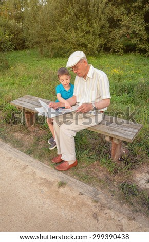 Senior man reading newspaper and cute child pointing an article with his finger sitting on park bench. Two different generations concept. - stock photo