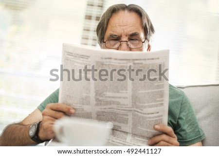 Senior man reading newspaper in home