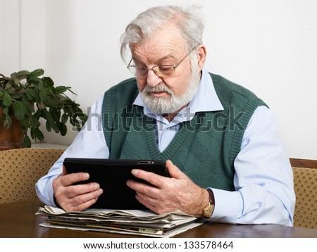 Senior man reading newspaper on digital tablet - stock photo
