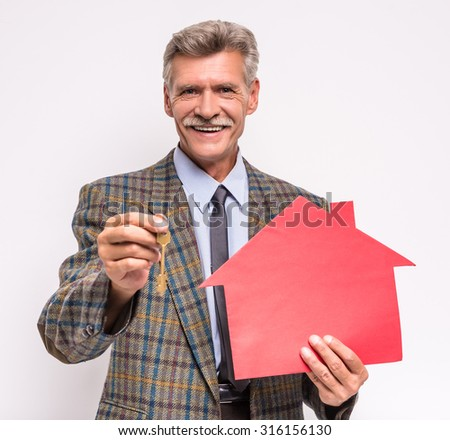Senior man realtor is holding a key and model of house. - stock photo