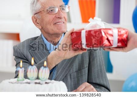 senior man receiving gift for birthday - stock photo