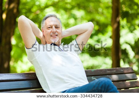 Senior man relaxing at the park - stock photo