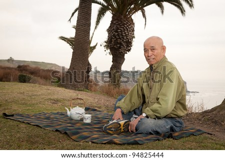senior man relaxing in beachside sitting on grass