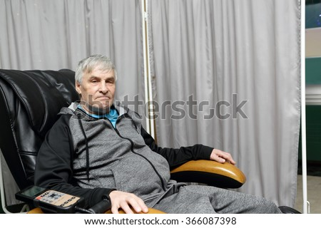 Senior man relaxing on a massage chair - stock photo