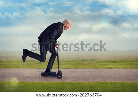 senior man riding a scooter active and energetic - stock photo