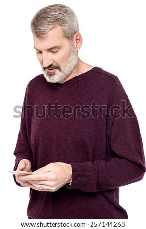 Senior man sending messages in his mobile phone