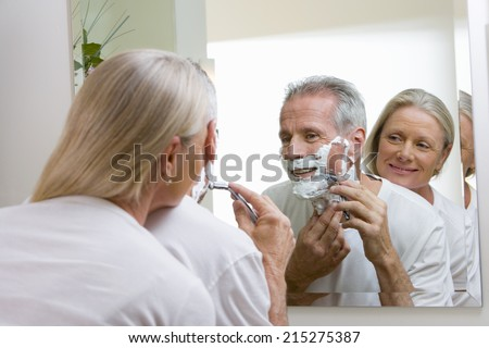 Senior man shaving at home, woman embracing man, watching, reflection in bathroom mirror, rear view