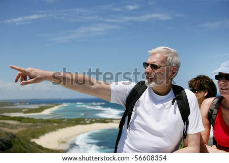 Senior man showing a direction with his finger to a senior group - stock photo