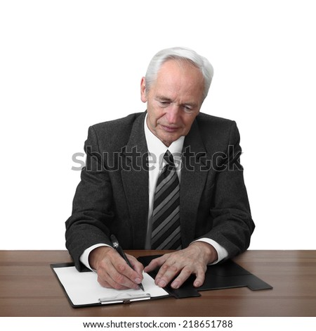 Senior man sits at table and writes document isolated on white background