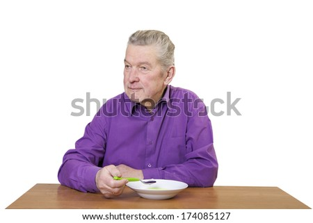 Senior man sitting and eating.