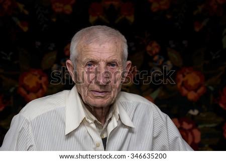 senior man sitting at his rural house  - stock photo