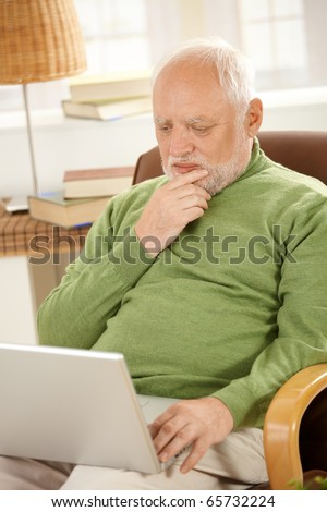 Senior man sitting at home, looking at screen of laptop computer, thinking.? - stock photo