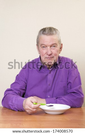 Senior man sitting at table.