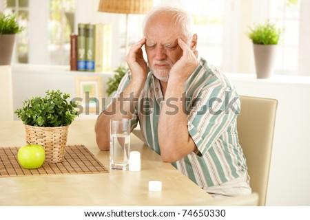 Senior man sitting at table, having bad headache, grimacing, taking medicine.? - stock photo