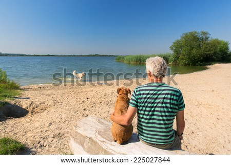 Senior man sitting at tree trunk with his dog in landscape with river - stock photo