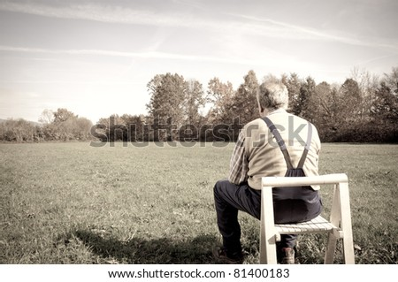 Senior man sitting in a chair on the field